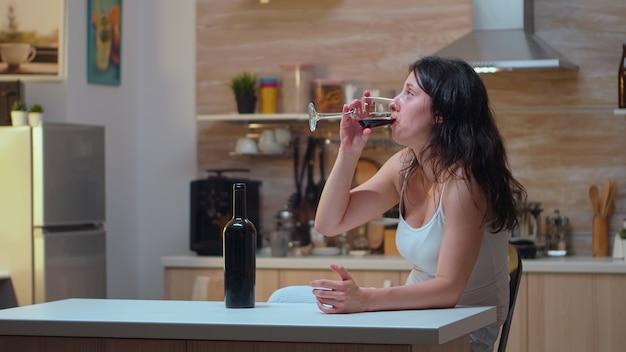 Uzależniona kobieta pije samotnie w domu. nieszczęśliwa osoba cierpiąca na migrenę, depresję, choroby i stany lękowe, wycieńczona z objawami zawrotów głowy, mająca problemy z alkoholizmem.