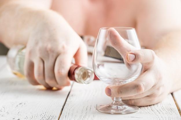 Uzależniony od alkoholu mężczyzna przy stole. smutny przygnębiony dorosły mężczyzna w kwarantannie
