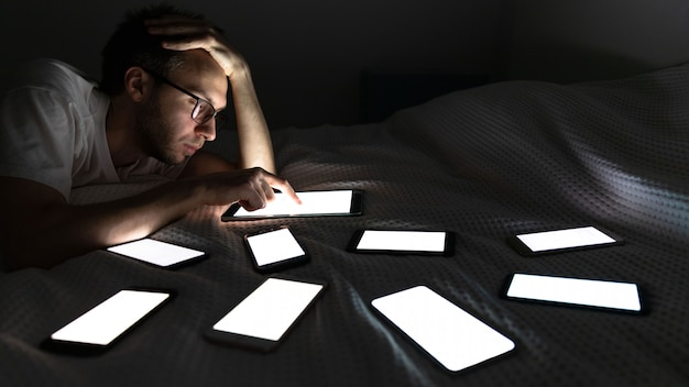 Uzależniony od gadżetu człowiek korzystający z tabletu późno w nocy, czatujący w sieciach społecznościowych, leżący w łóżku wokół zestawu włączonego telefonu