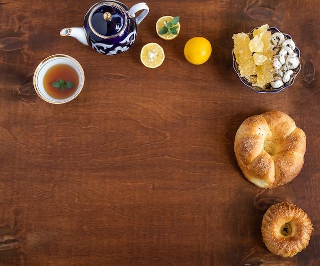 Uzbecki czajniczek i filiżanka herbaty z pustą przestrzenią kopii cukru i cytryny na drewnianym tle