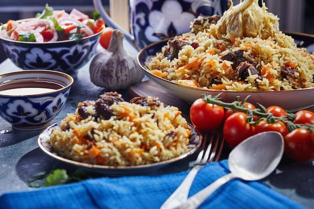 Uzbecki pilaw w autentycznym niebiesko-złotym naczyniu, nakręcony na niebieskim tle z pomidorami, czosnkiem i herbatą