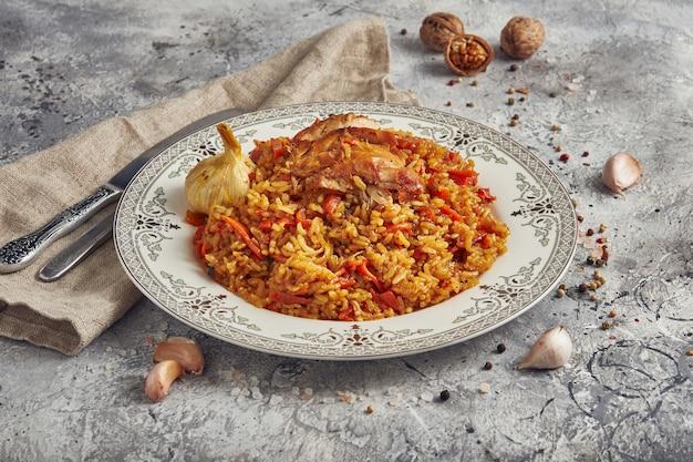 Uzbecki pilaw z jagnięciną i marchewką na talerzu, jasnym tle