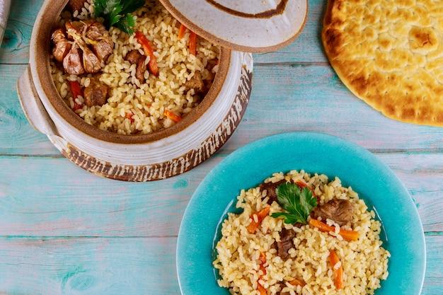 Uzbecki pilaw z ryżem, mięsem, marchewką i czosnkiem w glinianym garnku.