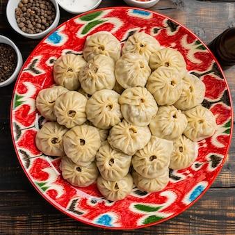 Uzbeckie gotowane manti lub manty pierogi w tradycyjnej misce na rustykalnym drewnianym stole.