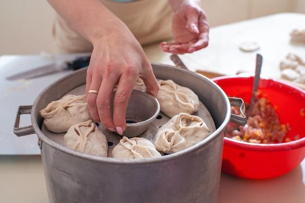 Uzbeckie narodowe manty spożywcze, takie jak pierogi, na specjalnym parowcu z kobietą trzymającą w dłoni. rama pozioma