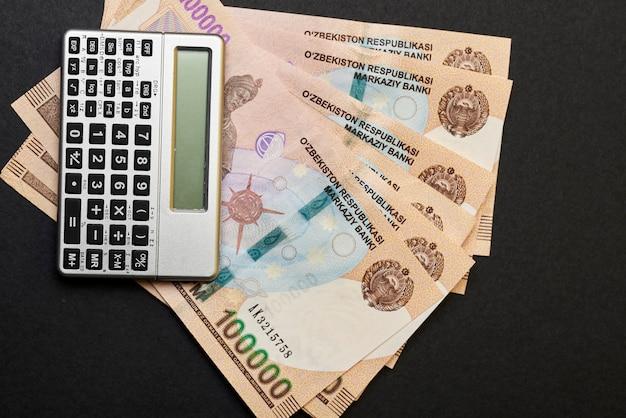 Uzbeckie pieniądze i kalkulator na czarnym tle uzbeckie sumy i kalkulator