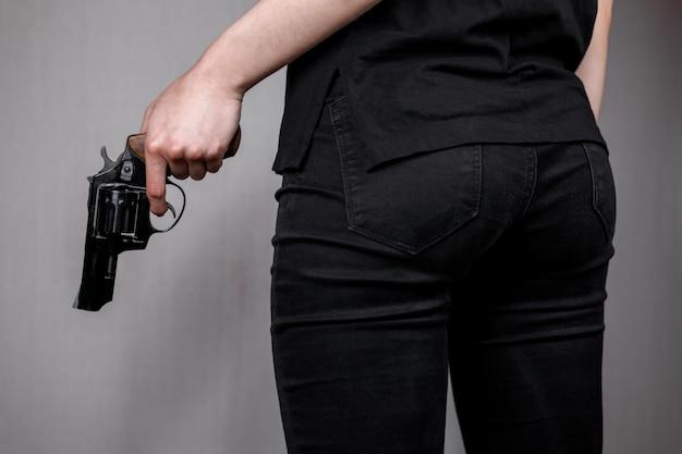 Uzbrojona dziewczyna w czarnych dżinsach chowa pistolet za plecami. ukryte zagrożenie zabójca.