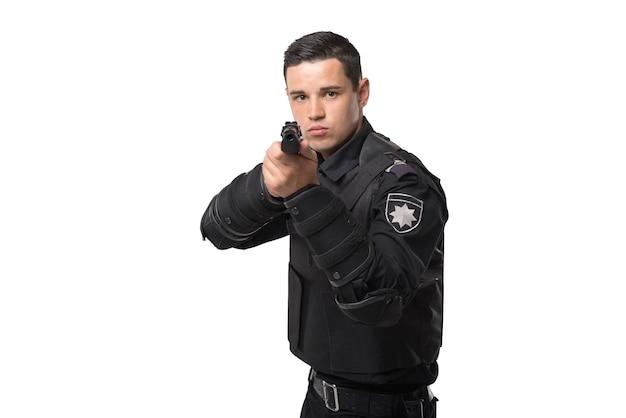 Uzbrojony policjant celuje z pistoletu