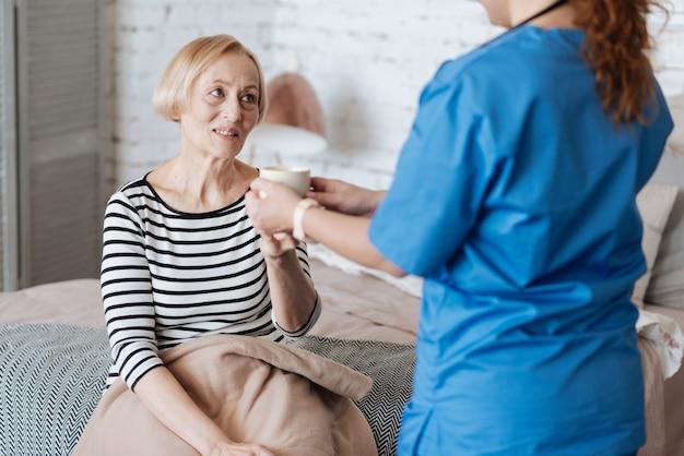 Uzdrawianie z życzliwością. delikatna, krucha ładna kobieta siedzi na łóżku przykryta kocem i dziękuje lekarzowi za pomoc w leczeniu