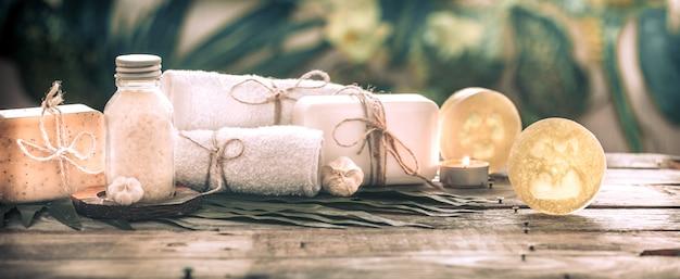 Uzdrowiskowe mydło ręcznie robione z białymi ręcznikami i solą morską, kompozycja tropikalnych liści ze świecą, tło drewniane