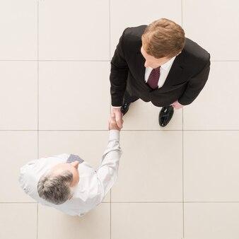 Uzgadnianie partnerów biznesowych. widok z góry dwóch biznesmenów ściskających ręce