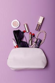 Uzupełniał torbę z kosmetykami odizolowywającymi na różowym tle
