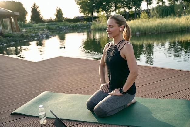 Uzupełnij zrelaksowaną kobietę w średnim wieku w sportowej odzieży uśmiechniętej siedzącej na macie podczas wykonywania jogi w