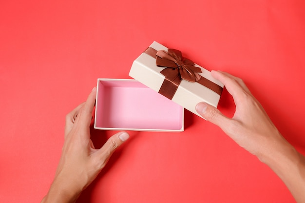 Użyj ręki, aby otworzyć pudełko upominkowe na czerwonym tle.
