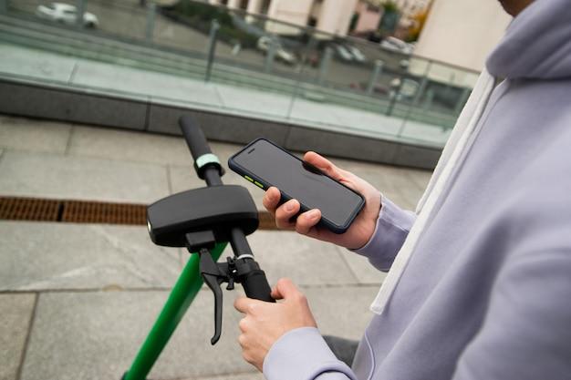 Użyj telefonu, aby wygodnie wypożyczyć skuter elektryczny. koncepcja szybkiej podróży. mężczyzna w szarym kapturem, trzymając smartfon i patrząc na mapy online. zielona hulajnoga elektryczna. koncepcja pojazdów.