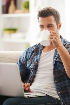 Uzyskiwanie najnowszych wiadomości online. przystojny młody mężczyzna pracuje na laptopie i pije kawę siedząc na kanapie