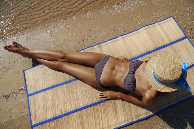 Uzyskiwanie złotej opalenizny. pełny długość odgórny widok piękna młoda kobieta w swimwear nakrycia twarzy z kapeluszem podczas gdy sunbathing na plażowym morzu, czas podróżować