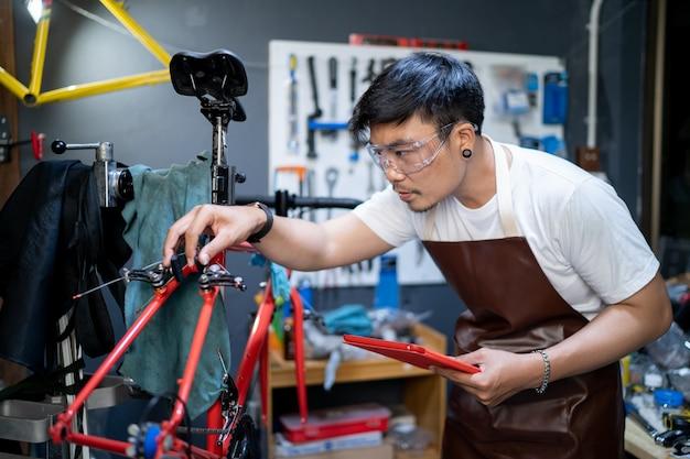 Używa tabletu, aby sprawdzić produkt. wejście do sklepu rowerowego zajmuje się rowerami klientów w celu sprawdzenia stanu.