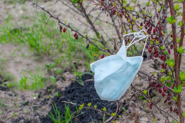 Używana maska medyczna na gałęzie krzewów. zakończenie kwarantanny koronawirusa, wiosna. opieka zdrowotna i ochrona z miejsca na kopię