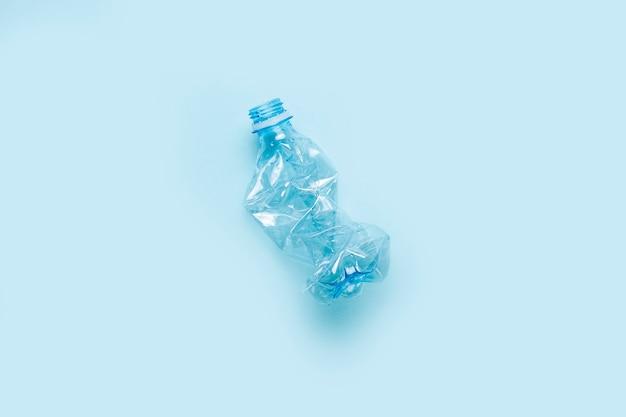 Używana plastikowa butelka na niebieskiej powierzchni. koncepcja wykorzystania plastiku. problem środowiskowy