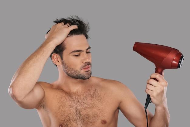 Używane, aby wyglądać idealnie. przystojny młody mężczyzna suszy włosy i ma zamknięte oczy, stojąc na szarym tle