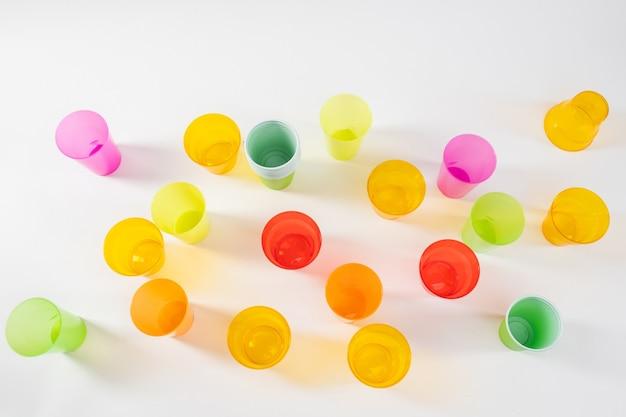 Używane i zapomniane. różne jasne i kolorowe plastikowe kubki stojące razem na białej powierzchni