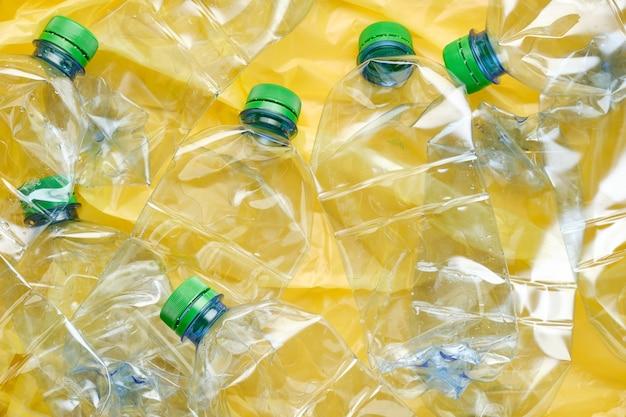 Używane plastikowe butelki wody z nakrętkami na żółtej ścianie. koncepcja recyklingu