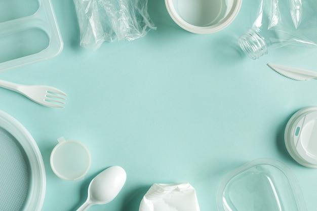 Używane plastikowe śmieci widok z góry ramki niebieskie tło papieru