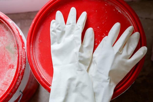 Używane rękawiczki lateksowe na wiadrze z farbą
