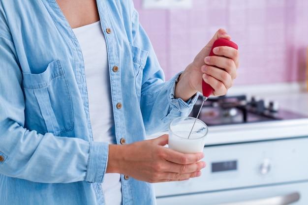 Używanie spieniacza do mleka do robienia aromatycznego cappuccino w kuchni w domu