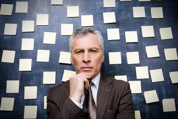 Używany do wielozadaniowości. rozważny starszy mężczyzna w stroju formalnym, patrzący na kamerę i trzymający rękę na brodzie, stojąc przed tablicą z samoprzylepnymi notatkami