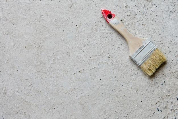 Używany duży płaski pędzel leży na betonowym tle
