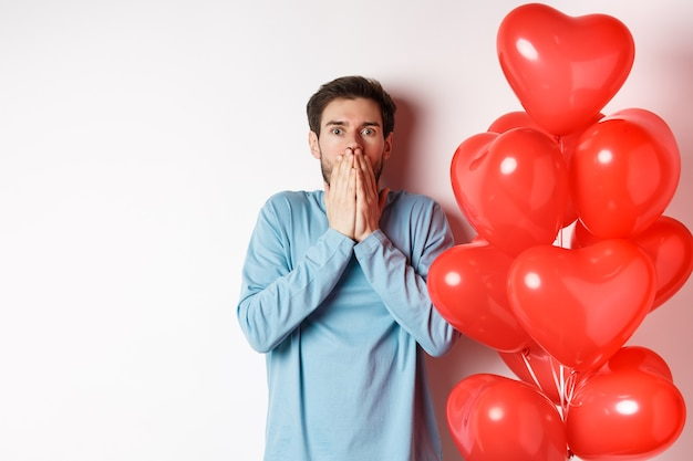 Valentine i związek. zmartwiony chłopak panikuje w dzień kochanków, stoi w pobliżu balonów z czerwonymi sercami i dyszy zszokowany, białe tło.