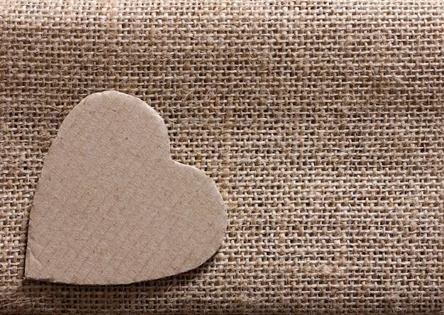 Valentine - symbol serca wycięty z opakowania kartonowego na tkaninie z konopi. skopiuj miejsce
