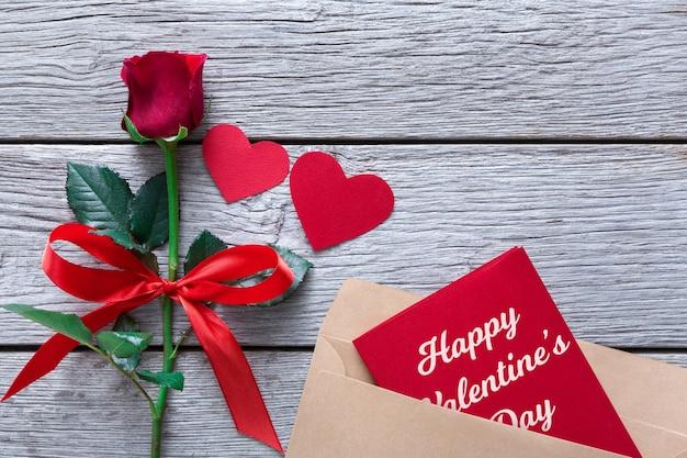 Valentine z czerwonym kwiatem róży i sercami z papieru czerpanego i kartką z życzeniami w kopercie na rustykalnym drewnie