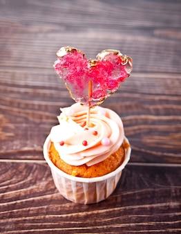 Valentines cupcake cream cheese frosting ozdobione lizakiem lizak serce na podłoże drewniane.