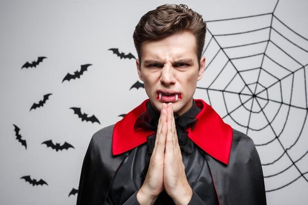 Vampire halloween concept - portret przystojny kaukaski w wampir halloween kostium modląc się.
