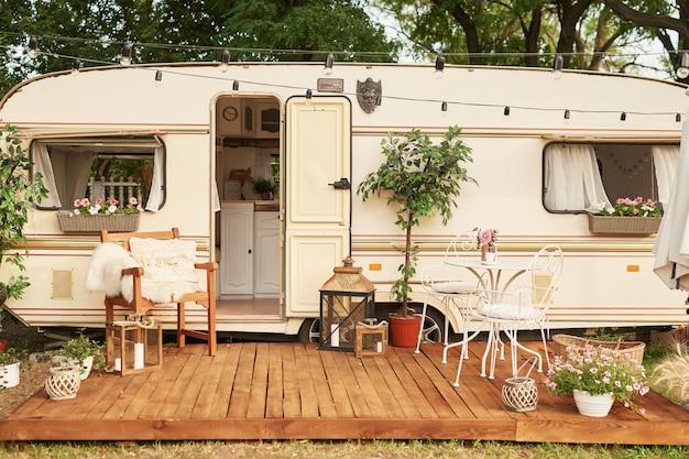 Van mobile home na zielonej trawie latem o zachodzie słońca, dom na kółkach