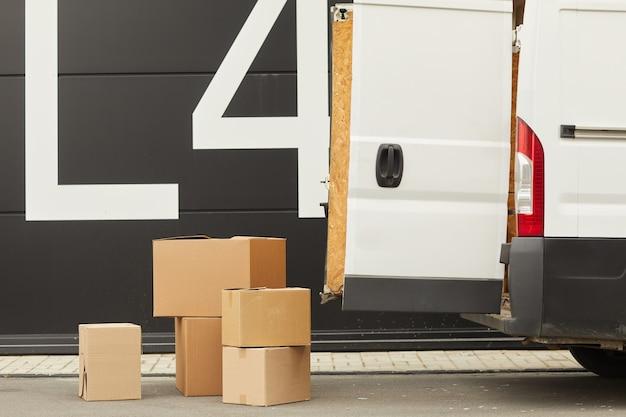 Van z otwartymi drzwiami i kartonami na ziemi to jest dostawa ładunku