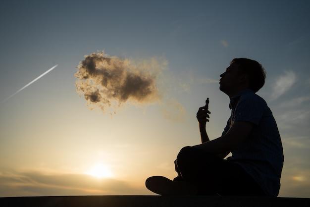 Vaping młody człowiek z, produkuje parę na tle zachodzącego nieba na nadmorskiej promenadzie, miejsce na tekst