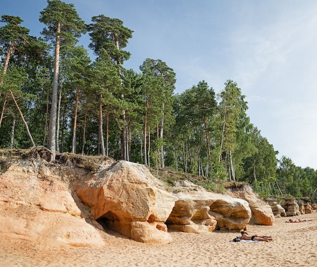 Veczemju klify czerwone skały, łotwa. plaża nad morzem bałtyckim. ludzie opalają się nad brzegiem bałtyku