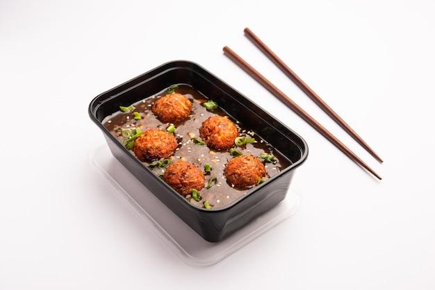 Veg manchurian zapakowane w czarny plastikowy pojemnik do zamówienia dostawy żywności online. popularny chiński przepis indyjsko-chiński!