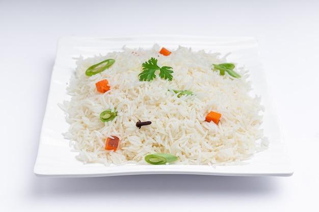 Veg pulao wykonane z warzyw ryżowych basmati i przypraw ułożonych w kwadratowej białej zastawie stołowej