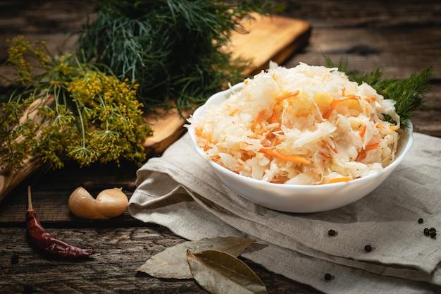 Vegan food - vegan food - kiszona kapusta z marchewką na drewnianej powierzchni, eko warzywa z marchewką na drewnianej powierzchni