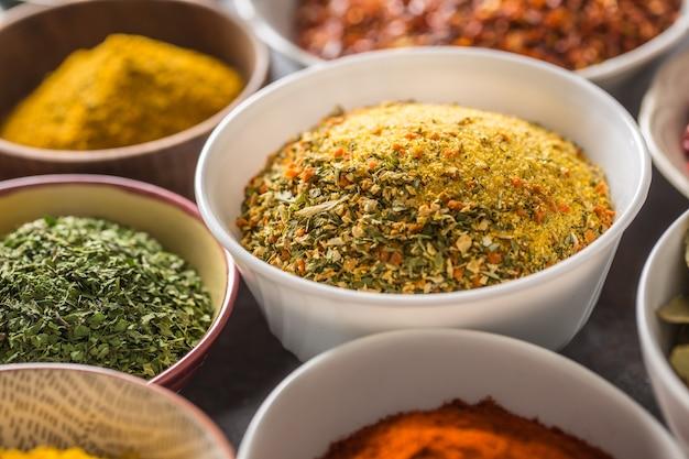 Vegeta i odmiany przypraw i ziół w miseczkach. suszone warzywa z solą i ziołami.