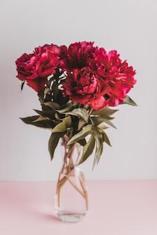 Vertical strzał czerwone peonie z zielonymi liśćmi w szklanym wazie. wiosna