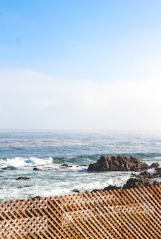 Vertical strzał drewniany ogrodzenie blisko skalistego brzeg i morza