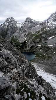 Vertical strzał jezioro otaczający górami pod chmurnym niebem