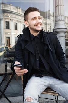 Vertical strzał ładny faceta obsiadanie na krześle w ulicie.