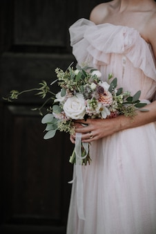 Vertical strzał panna młoda jest ubranym suknię ślubną trzyma kwiatu bukiet